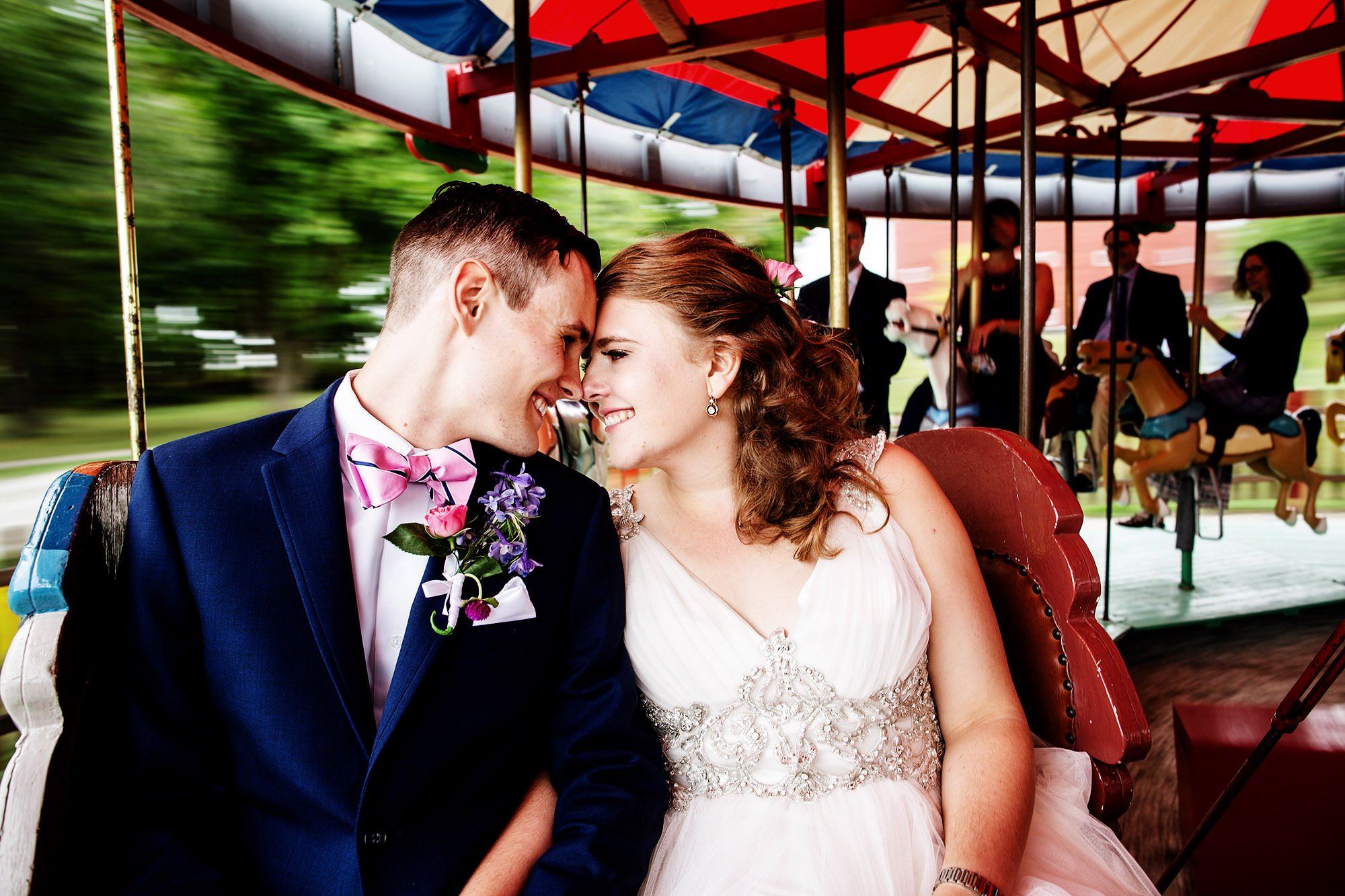 Shelburne Museum Wedding  I  The couple pose on the merry-go-round in Shelburne, VT.