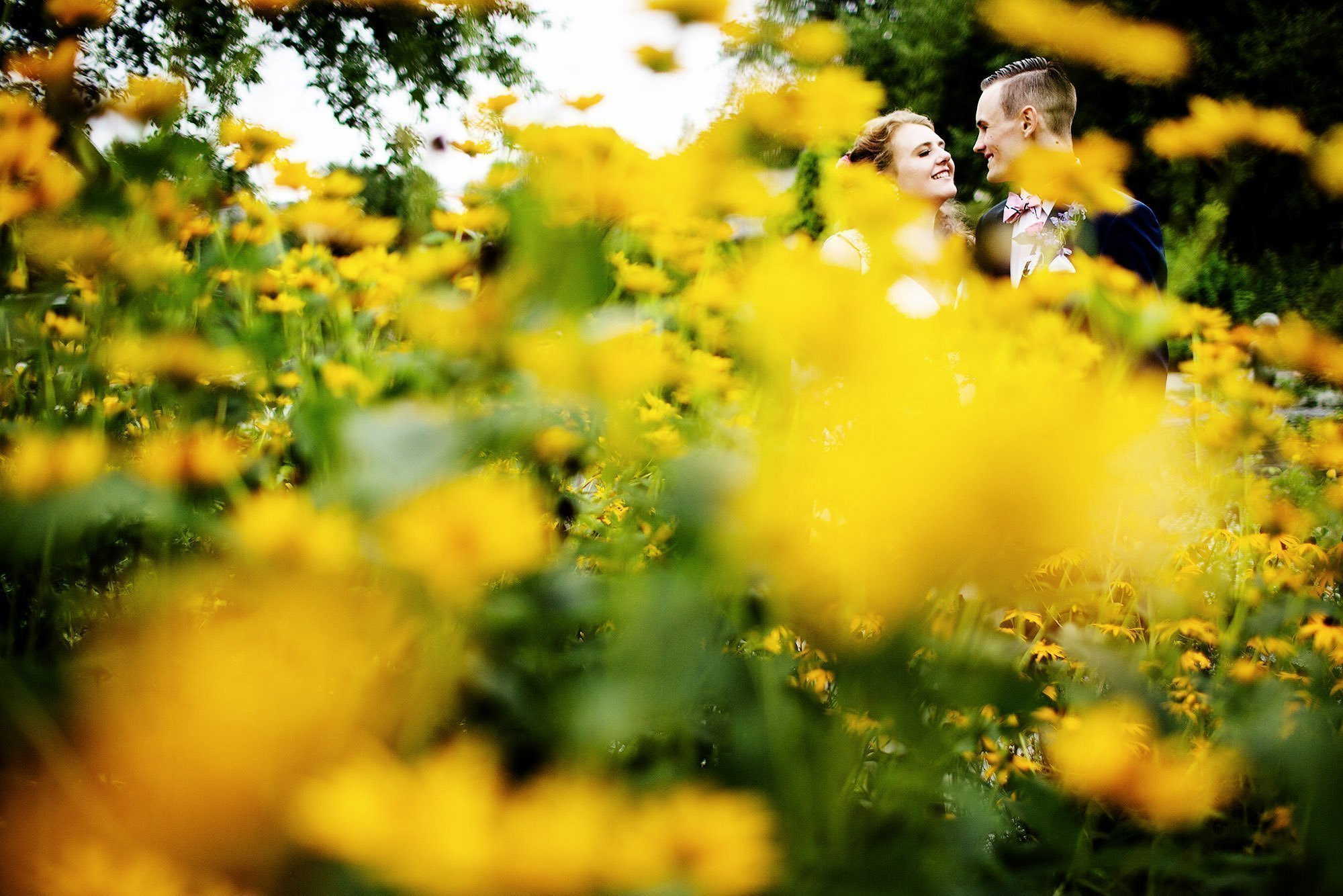 Shelburne Museum Wedding  I  The couple pose among beautiful yellow flowers following the ceremony.
