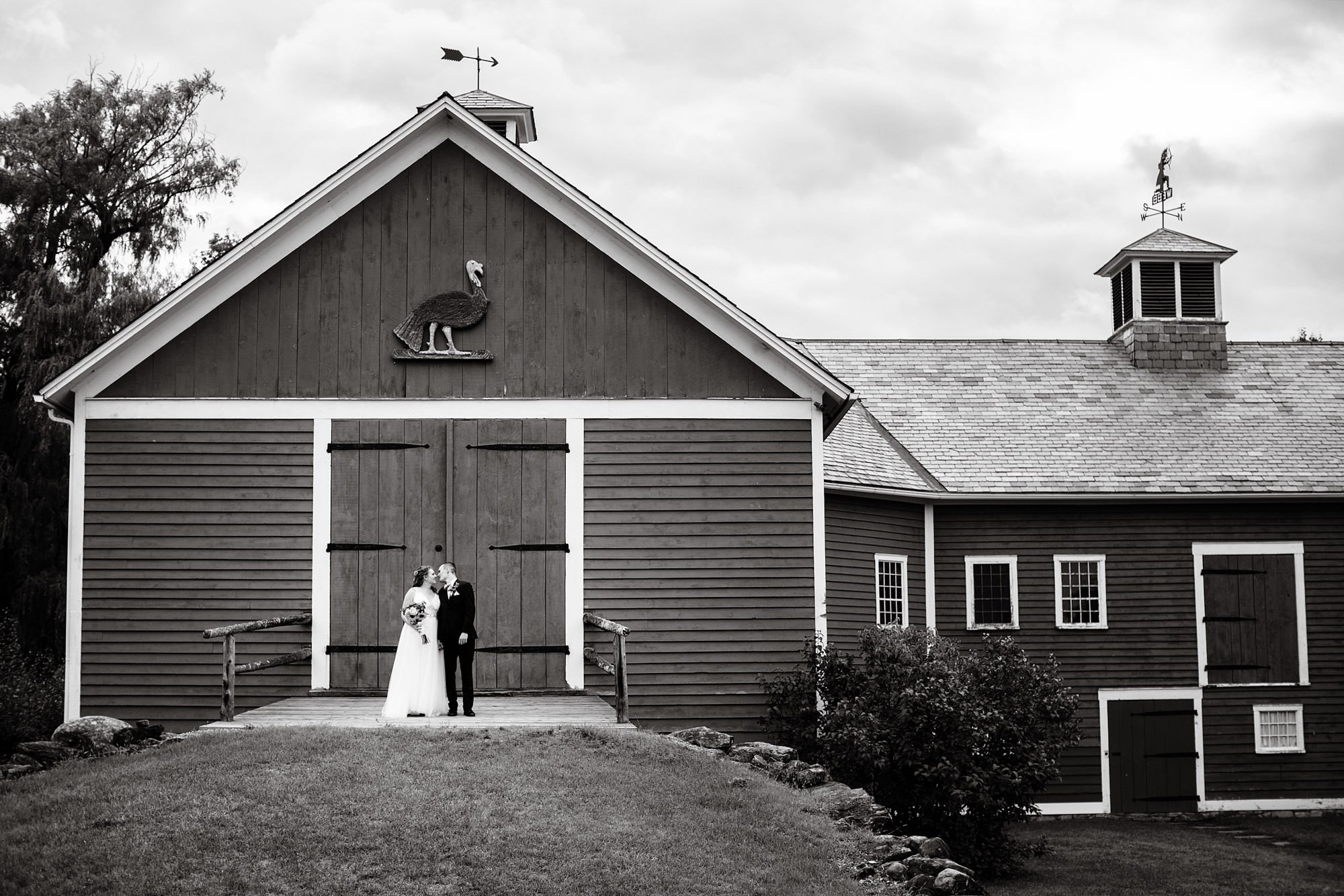 Shelburne Museum Wedding  I  The bride and groom kiss in front of a barn in Shelburne, VT.