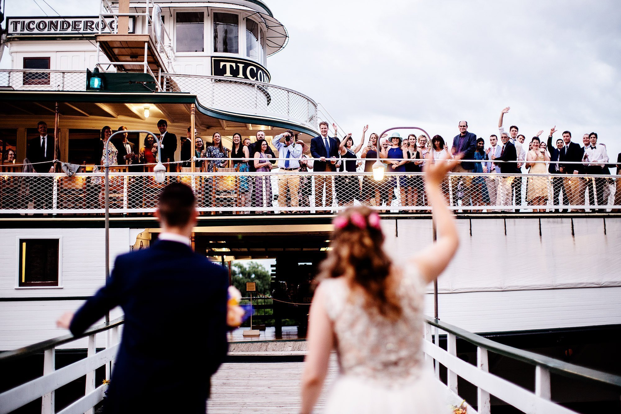 Shelburne Museum Wedding  I  The couple wave at guests on the Ticonderoga during cocktail hour