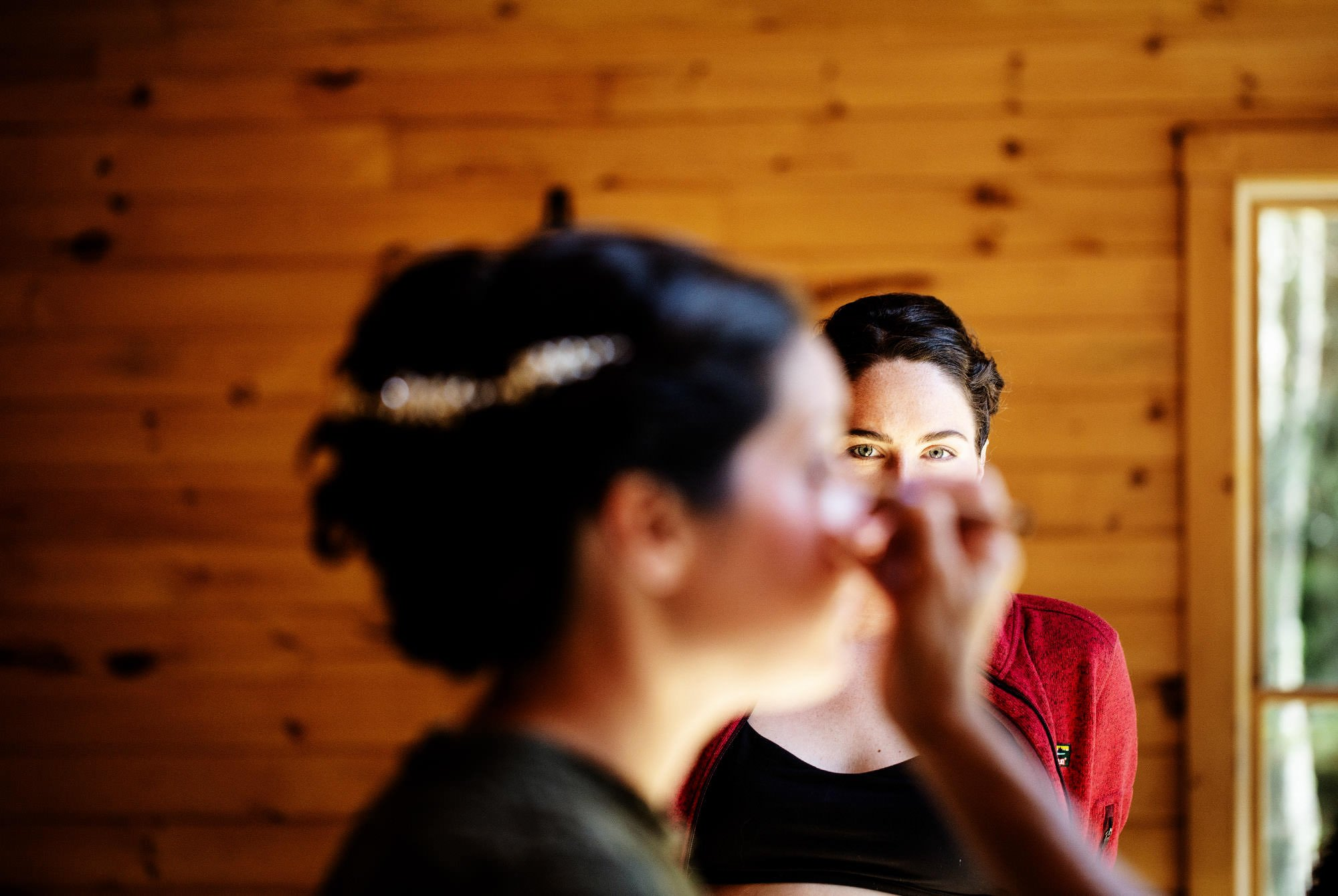 A bridesmaid watches as the bride puts on her makeup before the ceremony at this Maine Lakeside Cabin wedding.