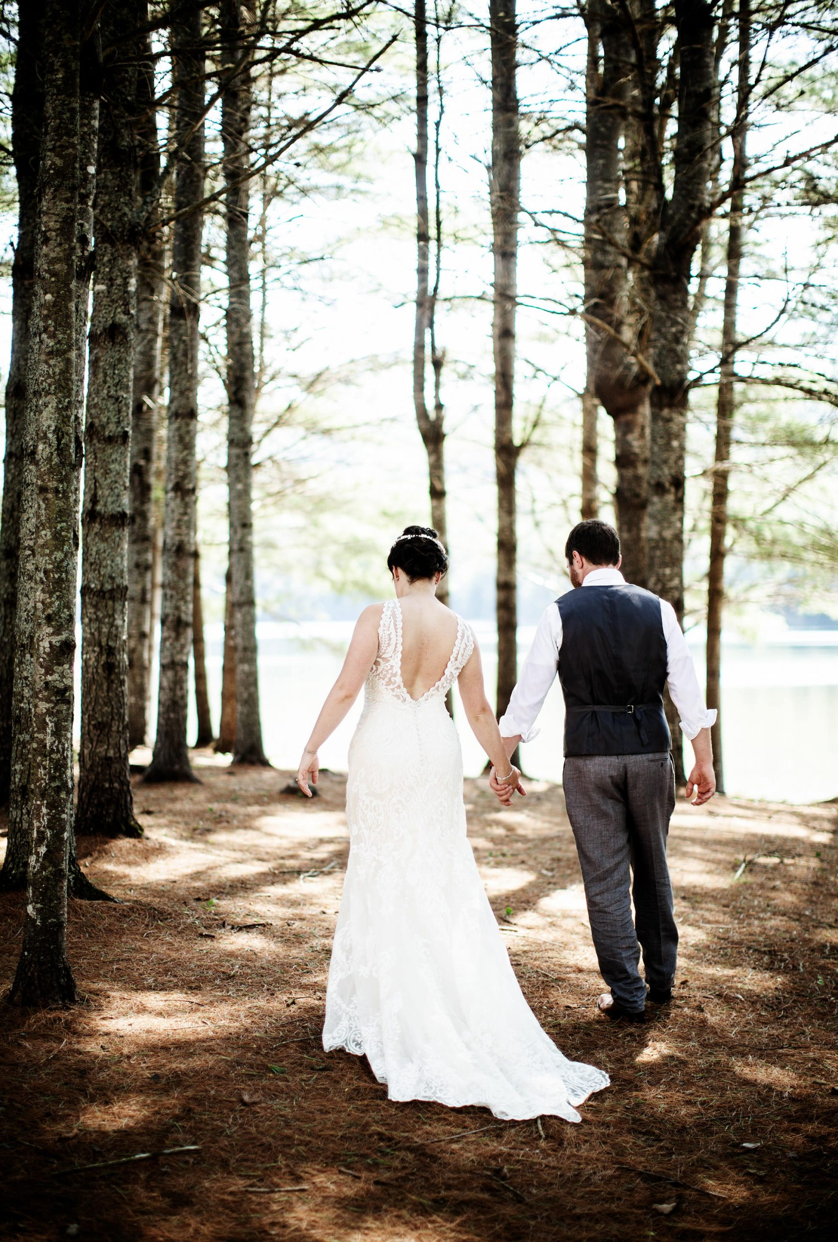 Maine Lakeside Cabin wedding  I  The bride and groom walk through the trees along Wyman Lake.
