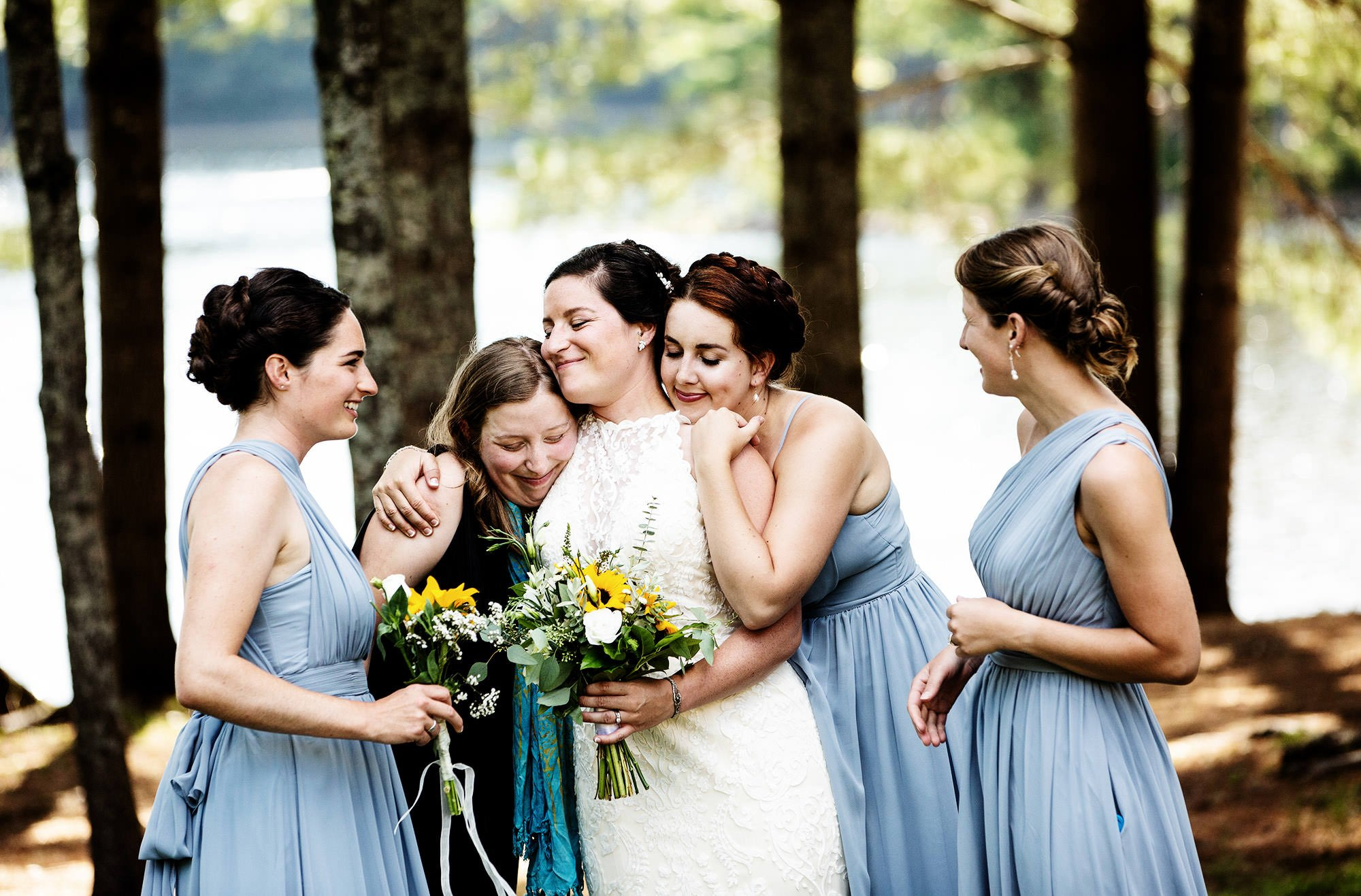 Maine Lakeside Cabin wedding  I  The bride hugs her friends following the ceremony.
