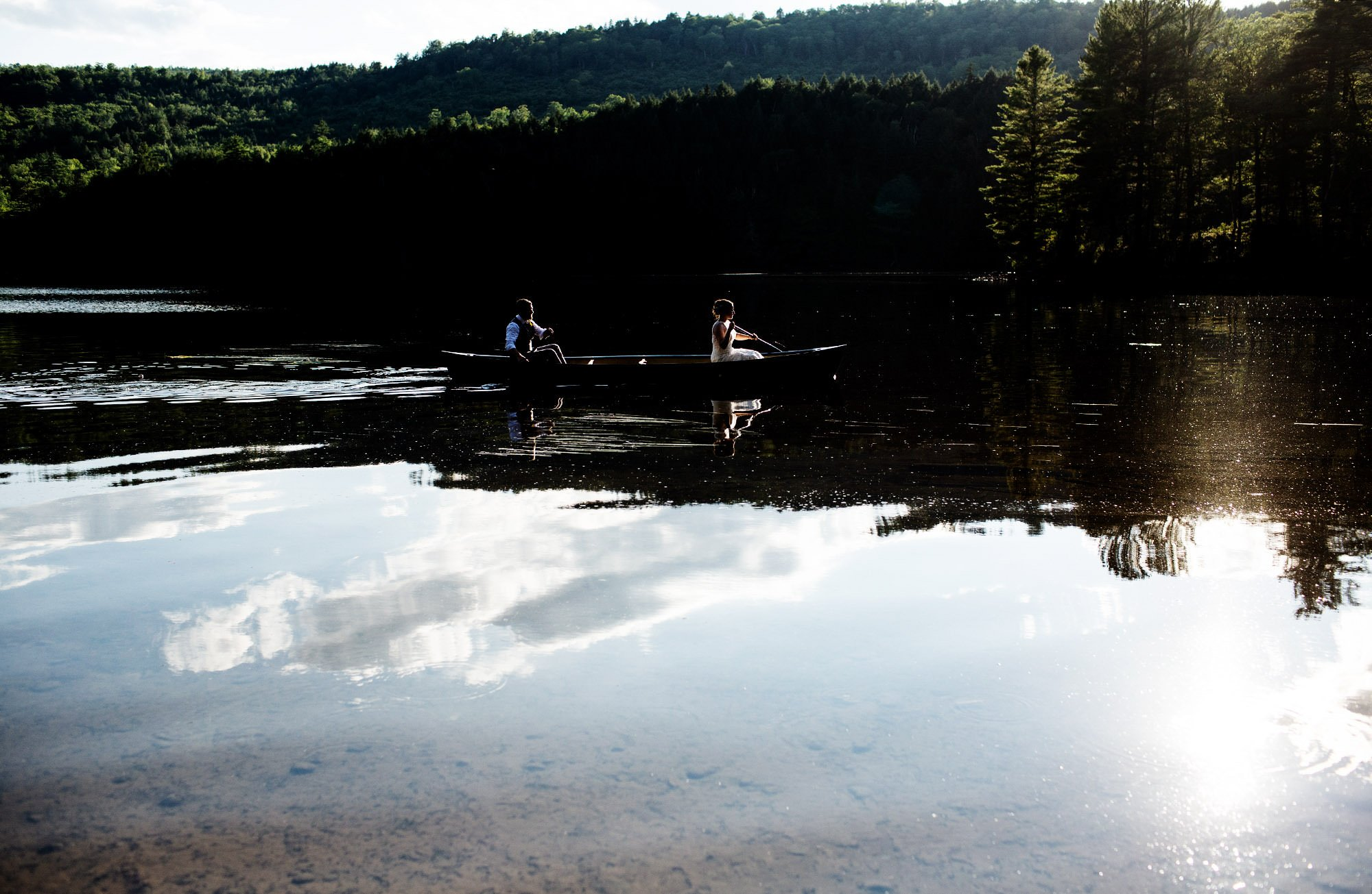 Maine Lakeside Cabin wedding  I  The couple row in a canoe following the wedding ceremony during sunset.
