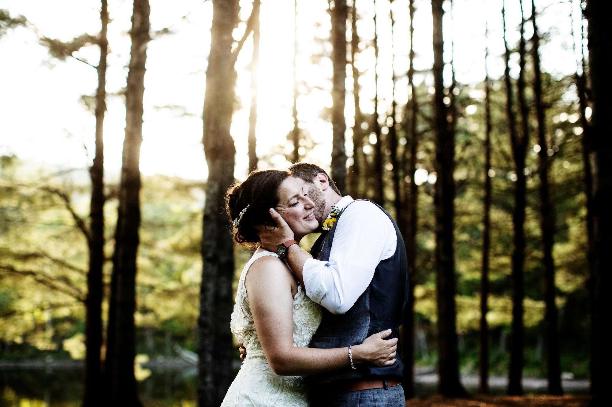 Maine Lakeside Cabin wedding  I  The bride and groom kiss during sunset on Wyman Lake.