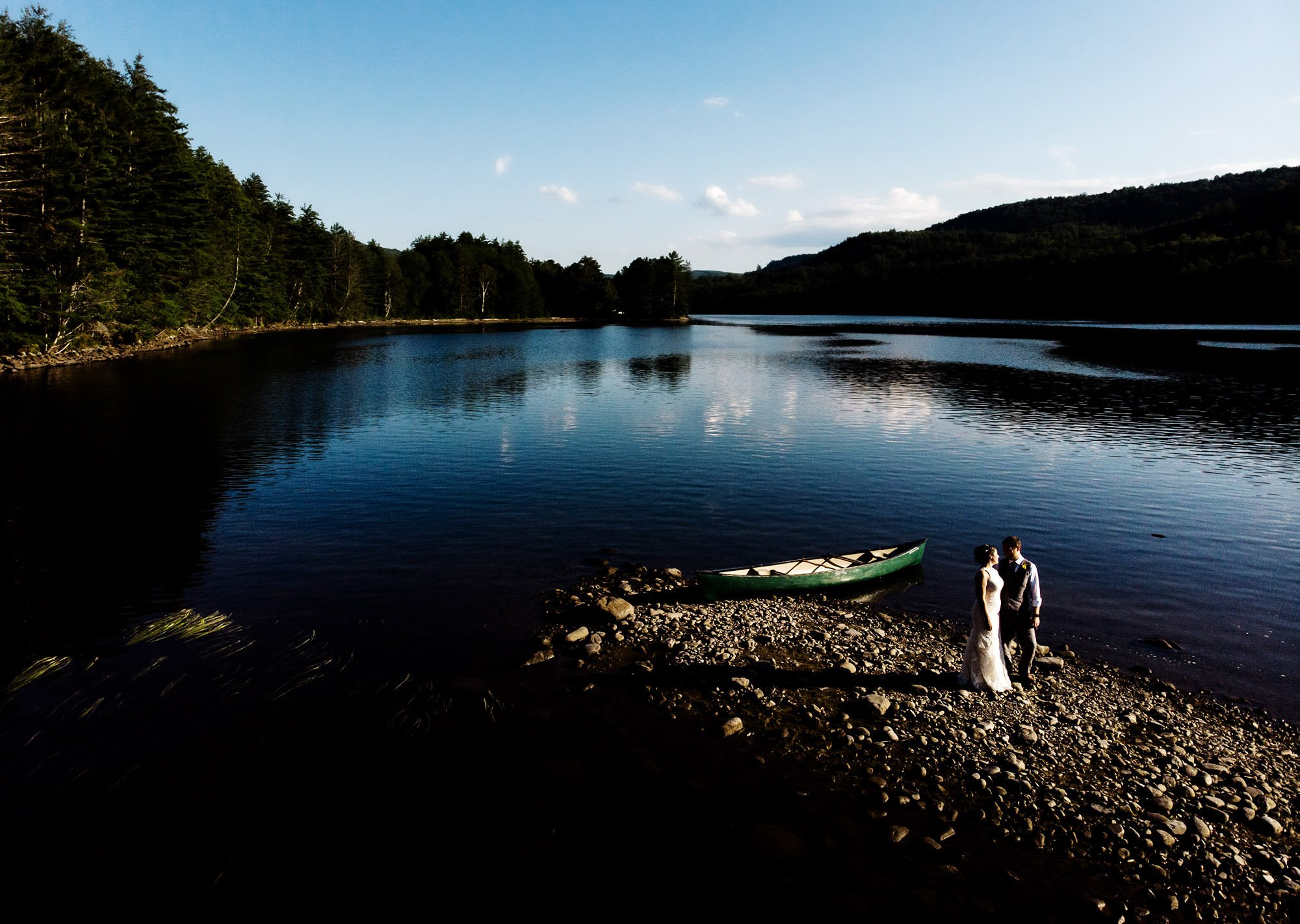 Maine Lakeside Cabin wedding  I  The bride and groom kiss during a drone portrait in Caratunk, ME on Wyman Lake.