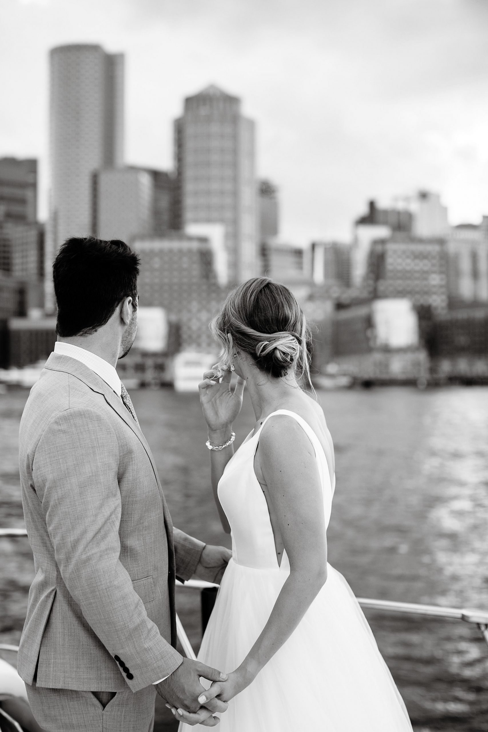 Boston Harbor Wedding I The bride and groom pose on the bow of a boat as they pass through Boston Harbor.