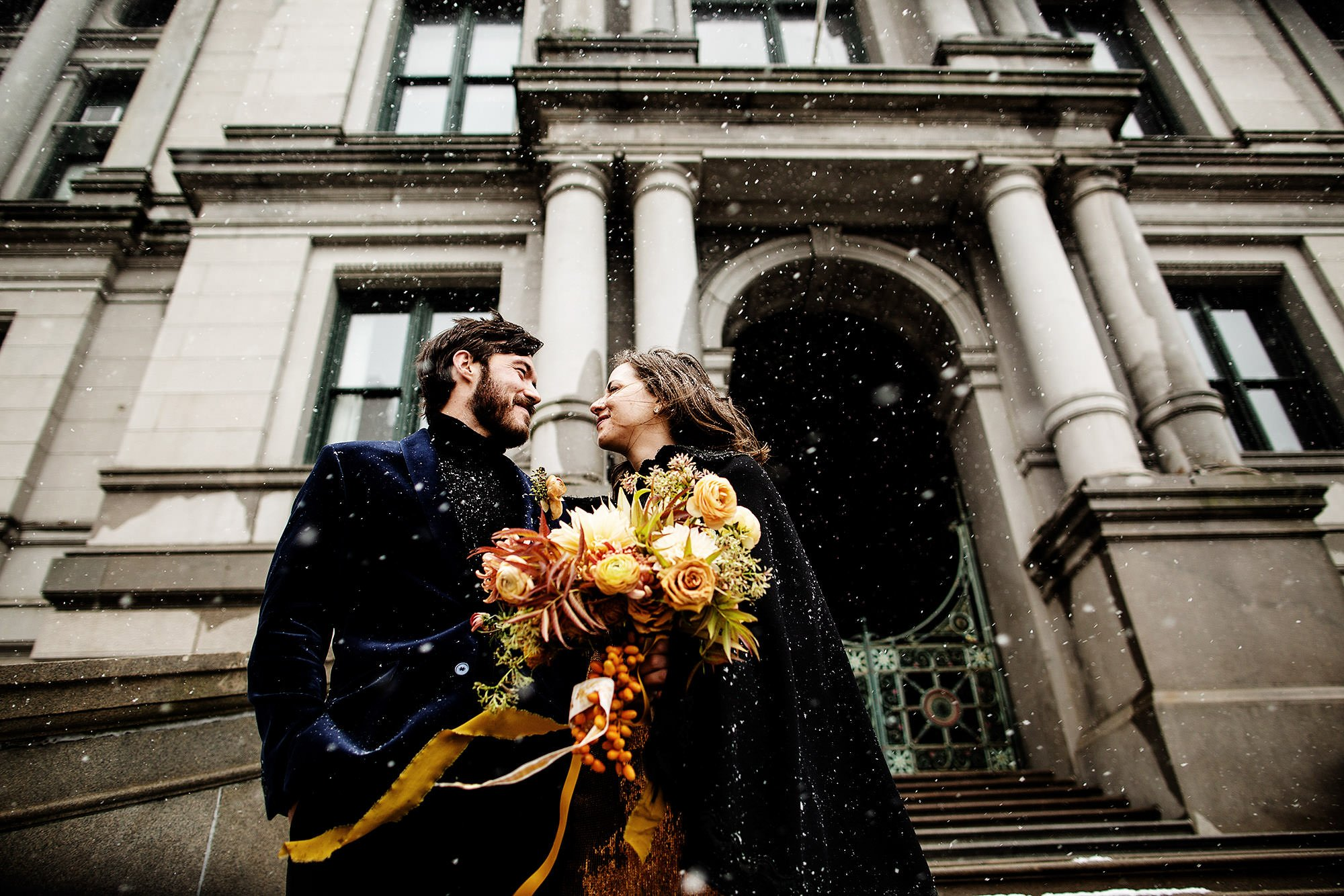 Providence City Hall Wedding  I  The couple stand on the steps of City Hall in the snow following their wedding ceremony.