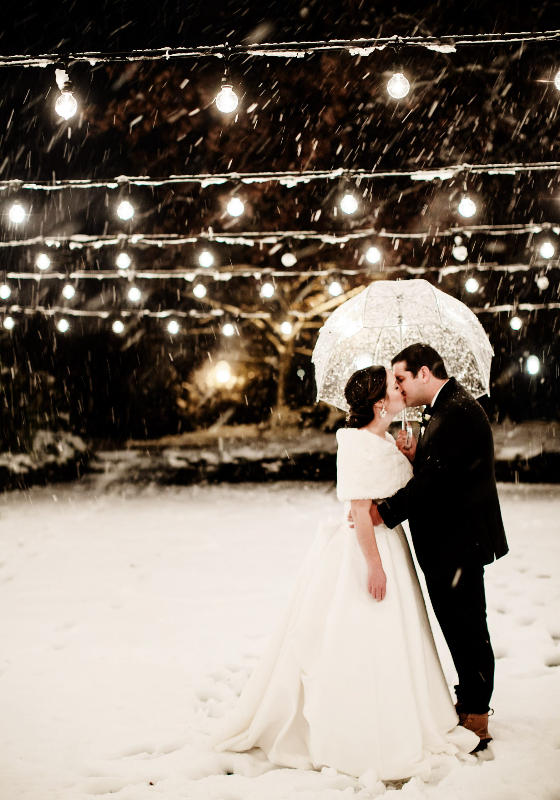 Bedford Village Inn Wedding  I  The bride and groom kiss under the lights in the courtyard in Bedford, NH as the snow falls.