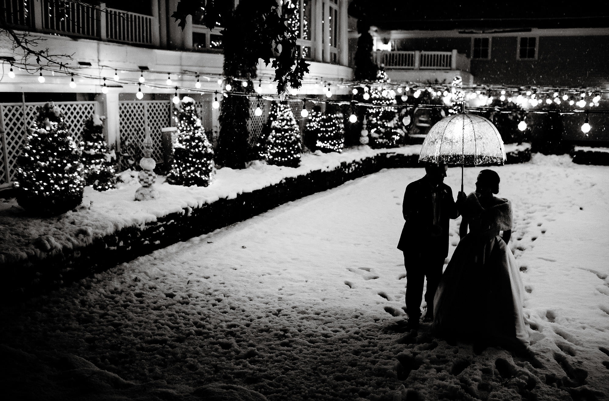 Bedford Village Inn Wedding  I  The couple walk through the courtyard in Bedford, NH as the snow falls.