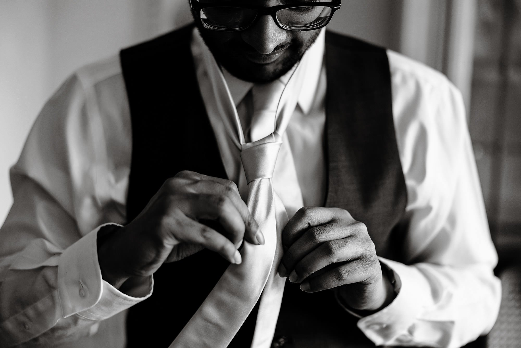 White Cliffs Country Club Wedding  I  The groom ties his tie prior to the wedding ceremony on Cape Cod.