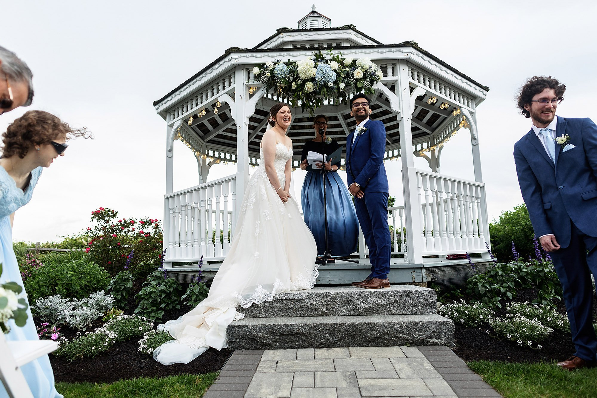 White Cliffs Country Club Wedding  I  The couple laugh during their wedding ceremony on Cape Cod.